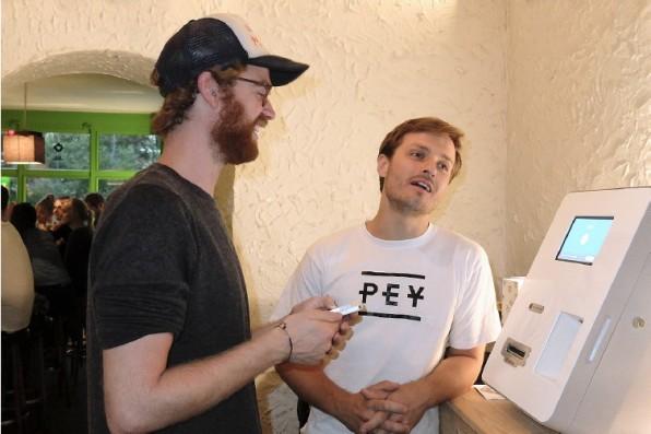Marius Beyer ist Assistent der Geschäftsführung bei PEY. Hier erklärt er einem Bitcoin-Interessierten, wie er mit dem Bitcoin-Automaten Euro in Bitcoin tauscht. Grundlegendes Interesse ist bei den Einsteigern vorhanden, allerdings ist der Nutzen vielen noch nicht klar. (Foto: Melanie Petersen)