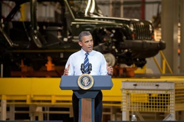 Komplettes Bild von Barack Obama, der eine Rede vor einer Fabrikationsstraße für Autos.